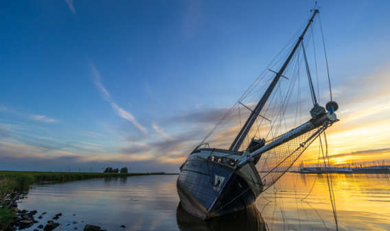 164629765 Scenic sunset at a stranded sailing boat near Lemmer, the Netherlands © Roelof, Fotolia_fw